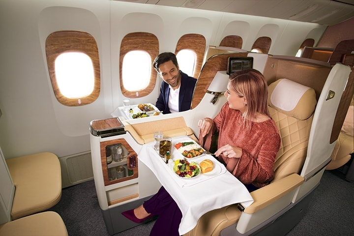 Bir çift, Boeing 777 uçakta Emirates Business Class'ta sohbet ediyor ve uçak içi yemeklerini yiyorlar