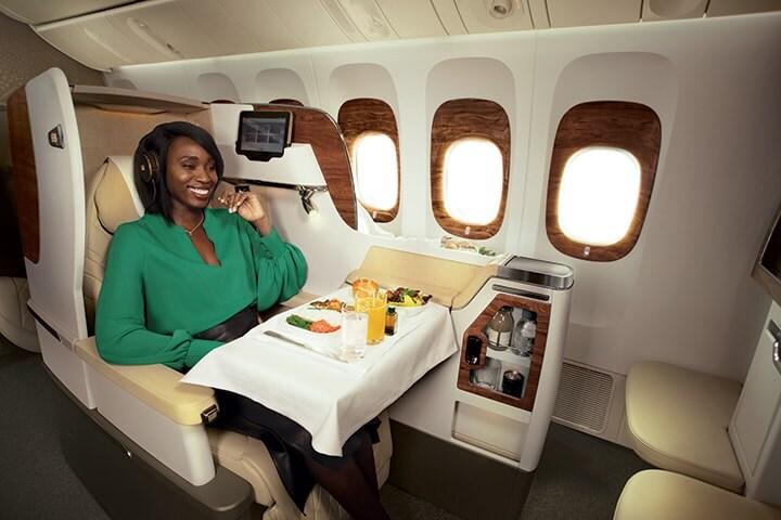 Bir kadın, Boeing 777 uçakta Emirates Business Class'ta oturuyor ve uçak içi yemeğinin tadını çıkarıyor