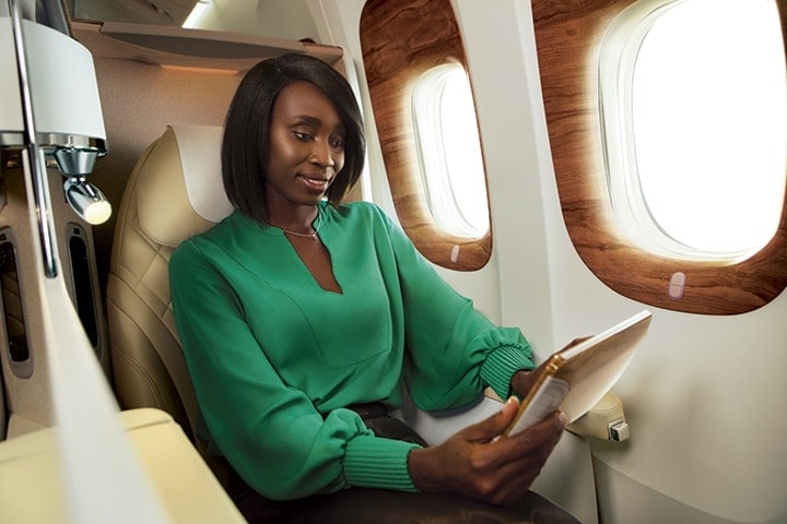 A woman in her seat in Emirates Business Class browsing what to watch on the Emirates inflight entertainment system, ice via her touchpad screen