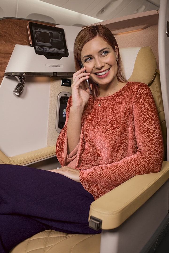 A woman sitting in her Emirates Business Class seat talking on her mobile phone