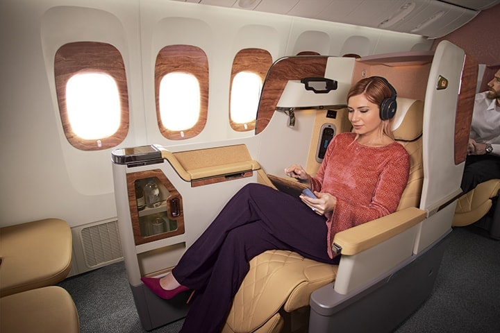 A woman in her seat in Emirates Business Class browsing what to watch on the Emirates inflight entertainment system, ice via her touchpad screen and wearing the Business Class headphones