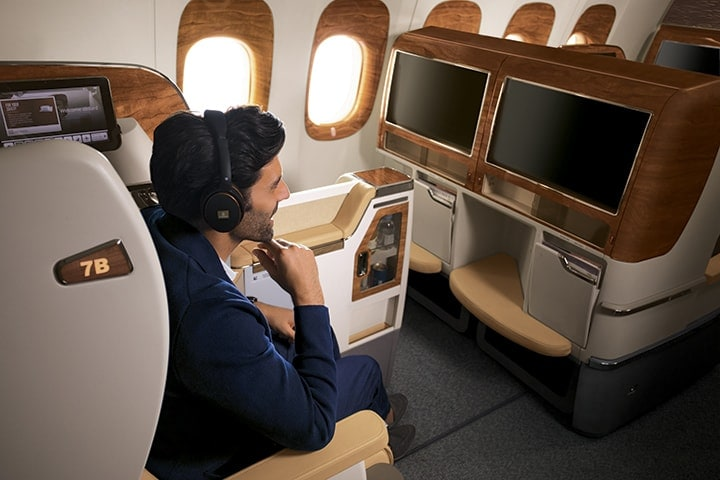 A man in his seat in Emirates Business Class looking at the widescreen TV and wearing Business Class headphones