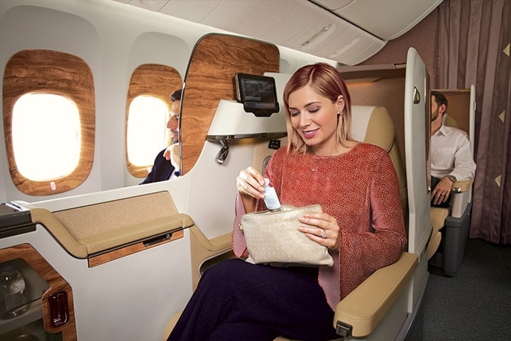 A woman opens her Bulgari amenity kit in Business Class to see the contents inside