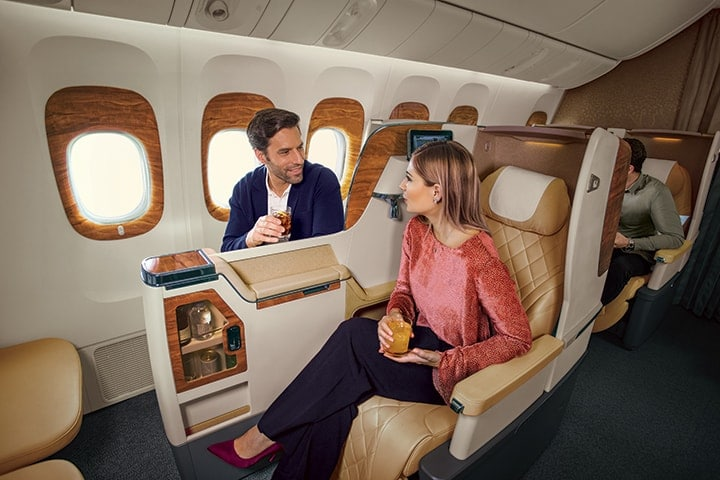 A couple chatting in their seats in Emirates Business Class on a Boeing 777