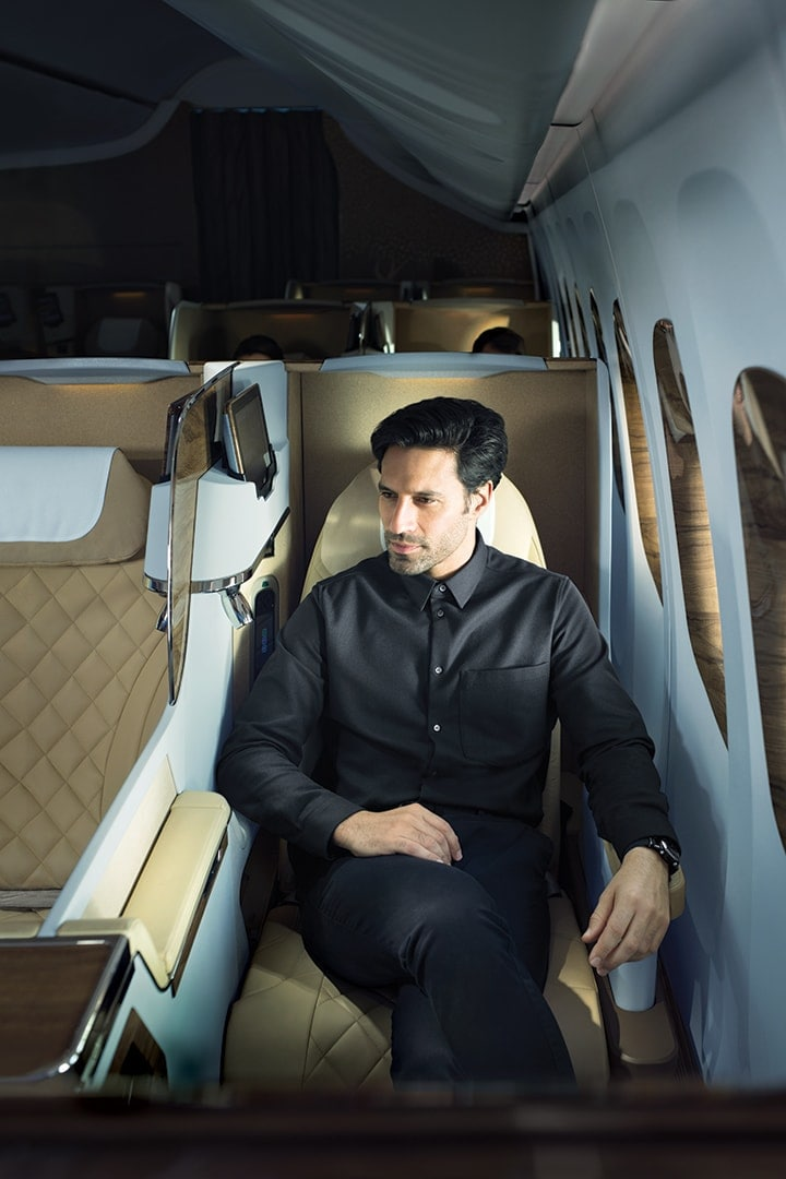A man comfortably sitting in Emirates Business Class on Boeing 777