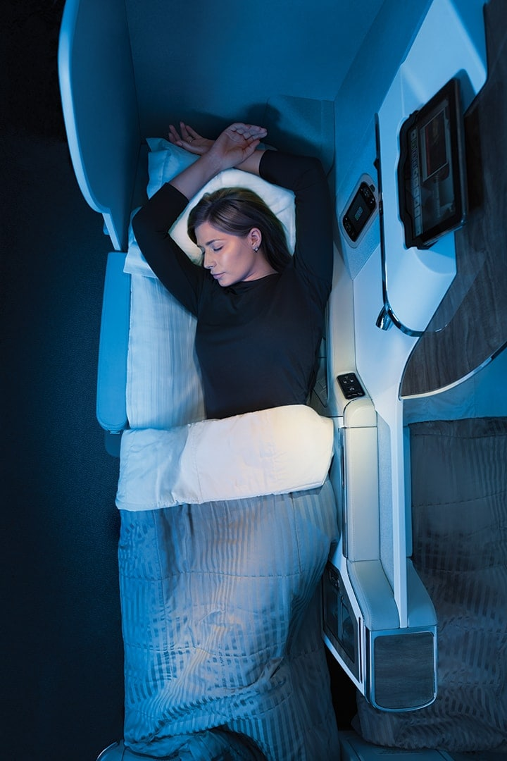 A woman is stretched out in bed in Emirates Business Class with her arms above her head on the pillow on a Boeing 777