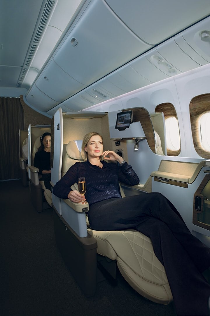 A woman enjoys a glass of wine while reclined in her Emirates Business Class seat on a Boeing 777
