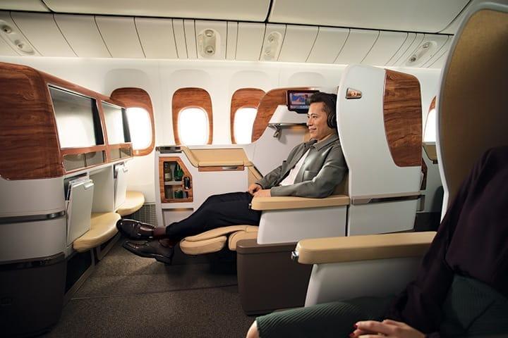 Bir adam, Emirates Business Class koltuğunda geniş ekran televizyonuna bakıyor ve Business Class kulaklıkları takıyor