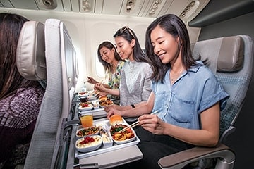 Three women in Emirates Economy Class on a Boeing 777 enjoying an Asian meal on board with chopsticks