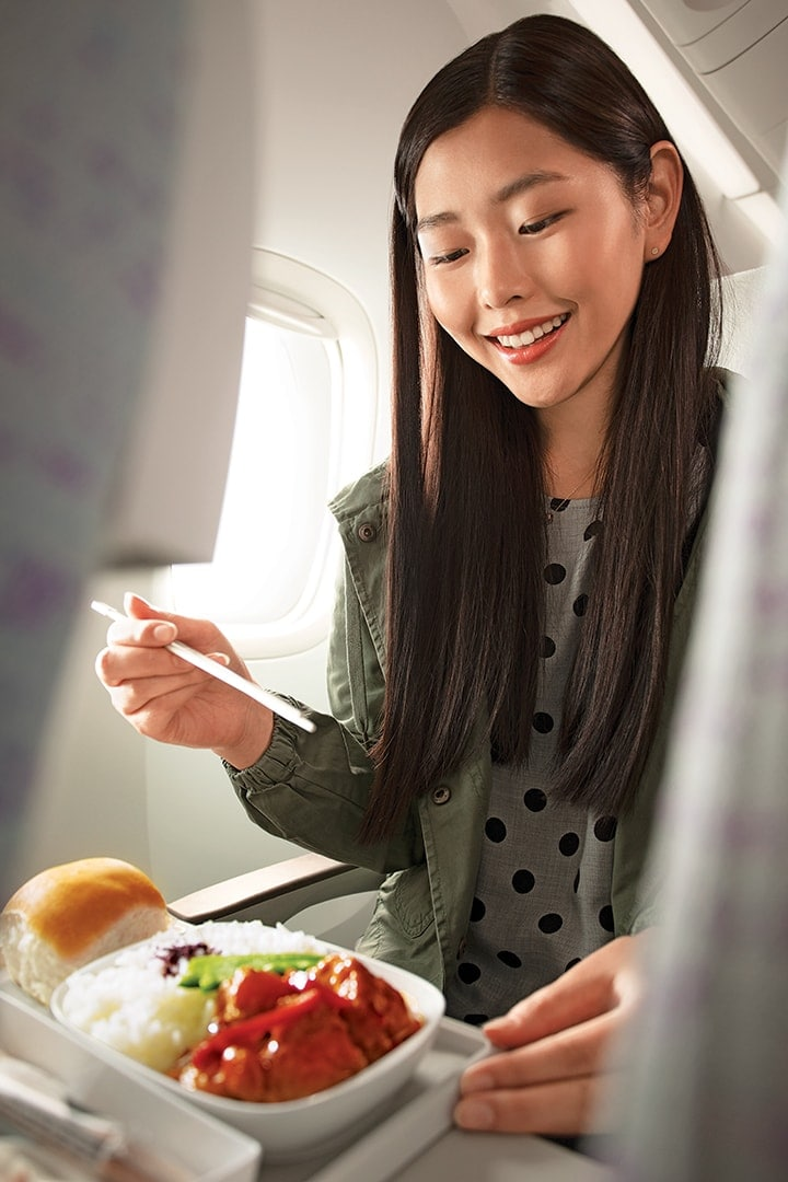 Asian woman enjoying an inflight meal with chopsticks in Emirates Economy Class on a Boeing 777