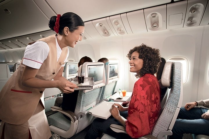 Smiling cabin crew serves a woman passenger a drink in a glass