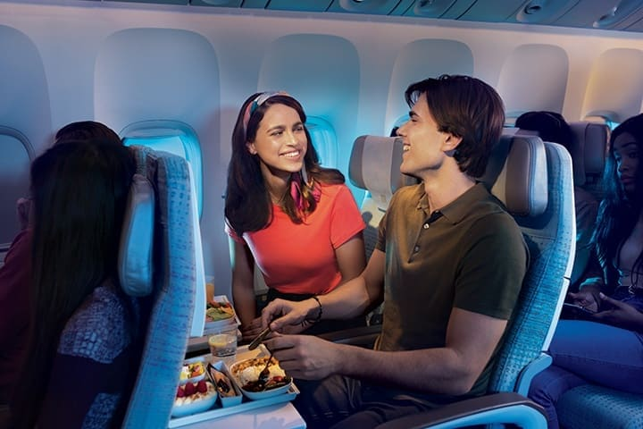 一对情侣坐在波音 777 飞机上的阿联酋航空经济舱内享用机上餐食。