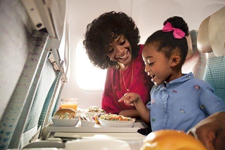 一位女士和一个女孩在波音 777 飞机上的阿联酋航空经济舱内浏览儿童机上餐饮