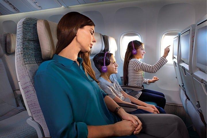 Семья сидит в Экономическом классе Эмирейтс на самолете Boeing 777, и дети смотрят на экраны ice