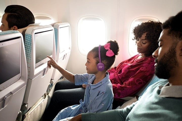 Young girl with purple ice headphones tapping on the ice inflight entertainment screen in Emirates Economy Class