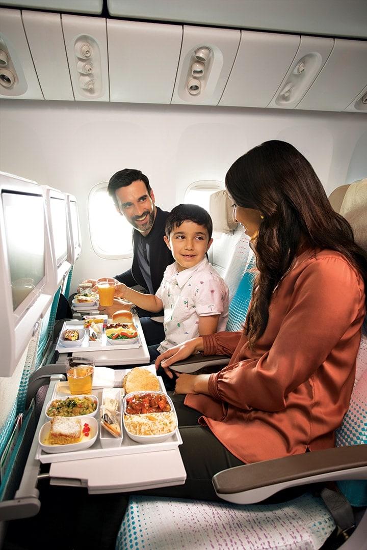 阿联酋航空经济舱内,一名儿童与一位男士和一位女士正在享用机上餐食