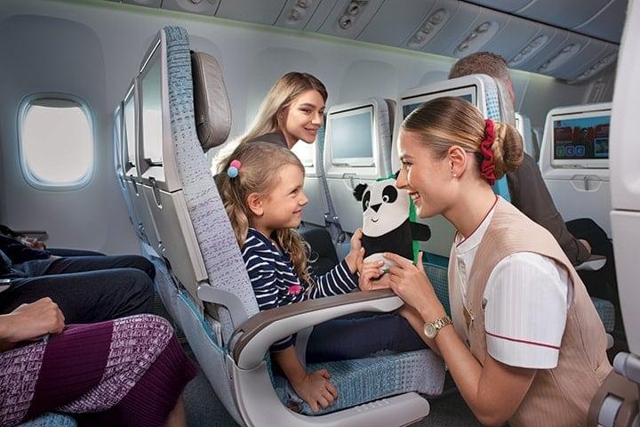 阿联酋航空经济舱内,女乘务员微笑着给满面笑容的小女孩熊猫娃娃