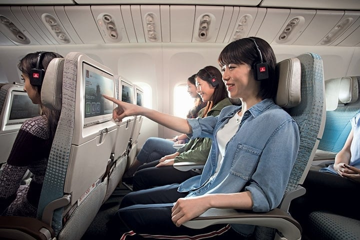 An Asian woman selecting entertainment on her touchscreen in Emirates Economy Class