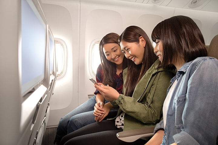Three women in Emirates Economy Class smiling and looking at a smartphone