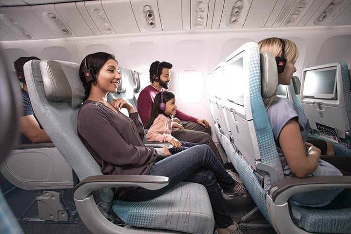 Smiling woman, girl child and man with headphones watching inflight entertainment in Emirates Economy Class