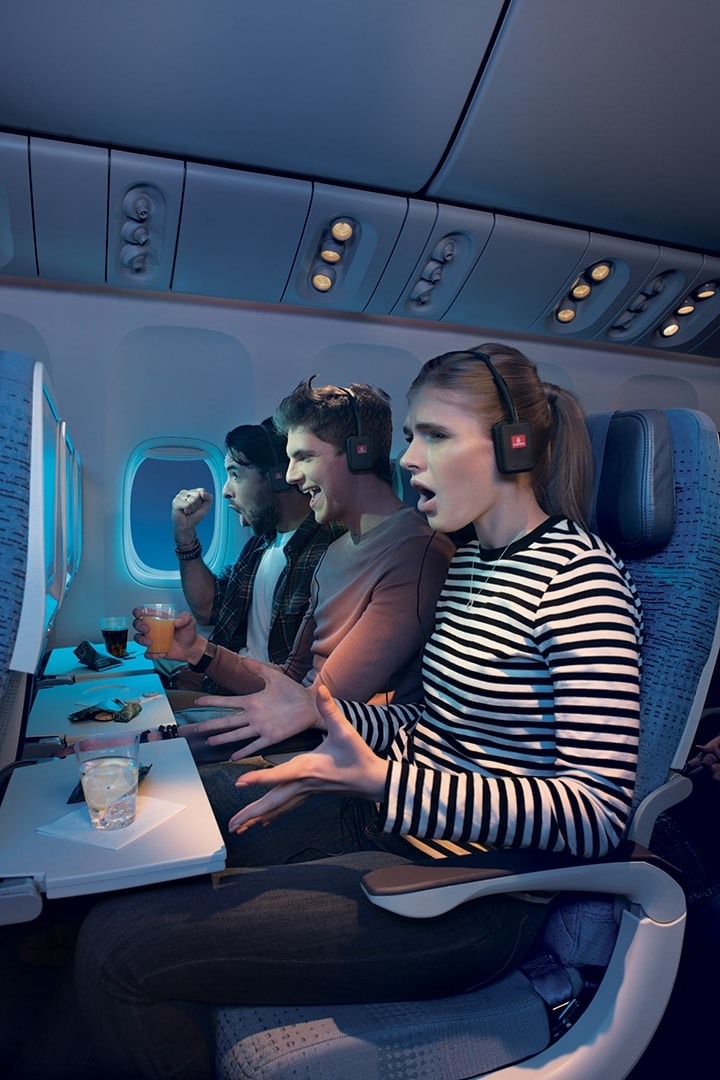 Two men and a woman watching their screens in Emirates Economy Class with exited expressions