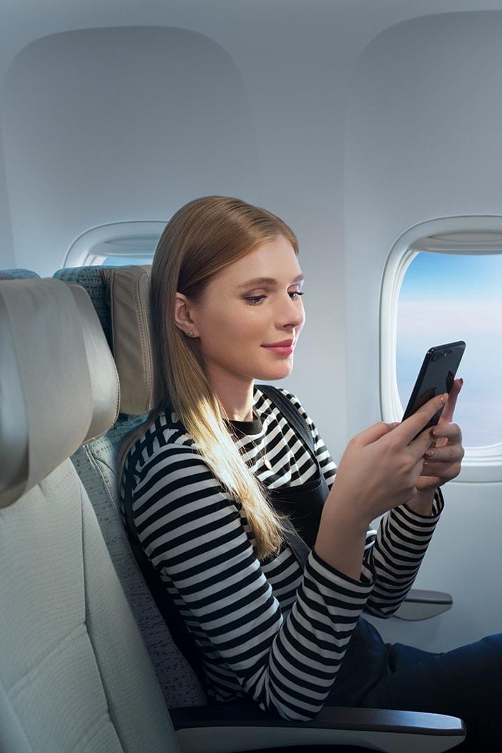 Молодая женщина смотрит на экран смартфона в Экономическом классе Эмирейтс