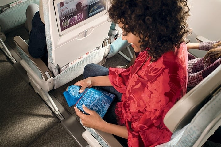 Woman holding a blue Emirates amenity kit with eye mask in Economy Class