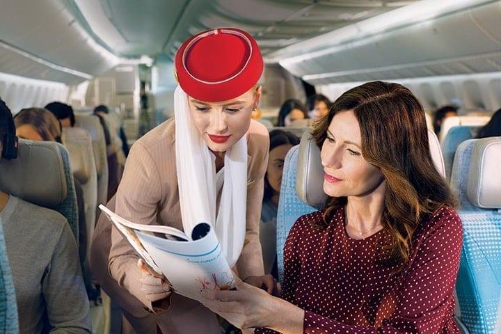 阿联酋航空经济舱内,一位女士与一名女乘务员在一起看机上杂志