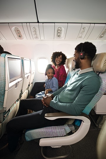 Man, woman and child smiling with ice headphones looking at each other on Emirates Economy Class