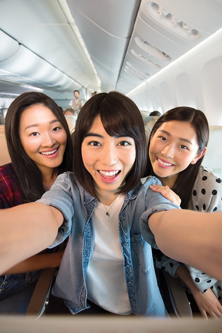 Three young women smiling and sitting in Emirates Economy Class