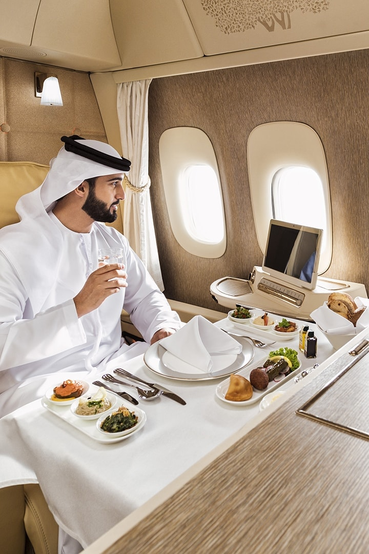 Man in Emirates First Class on a Boeing 777 sitting at a full table setting getting ready to eat his traditional Arabic Mezze onboard meal