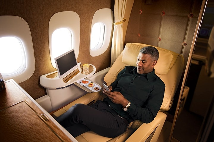 A man enjoys a beverage with canapes in Emirates First Class on a Boeing 777