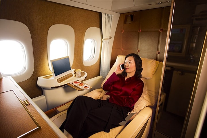 A woman enjoys a beverage with canapes in Emirates First Class on a Boeing 777