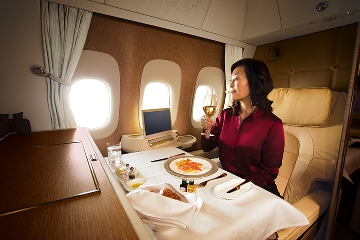 Woman in Emirates First Class on a Boeing 777 sitting at a full table setting getting ready to eat her onboard meal