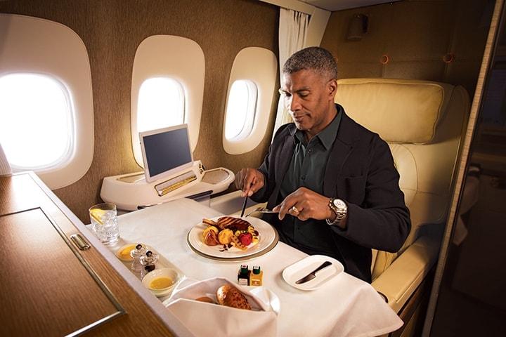 Bir adam, Boeing 777 uçakta Emirates First Class'ın tam donatılmış masasında yemeğini yemeye hazırlanıyor