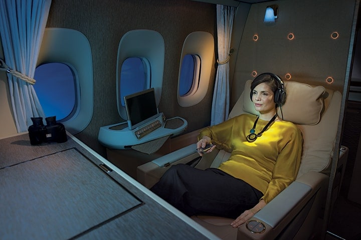 A woman watches her a movie at night on her inflight entertainment screen in Emirates First Class on the Boeing 777