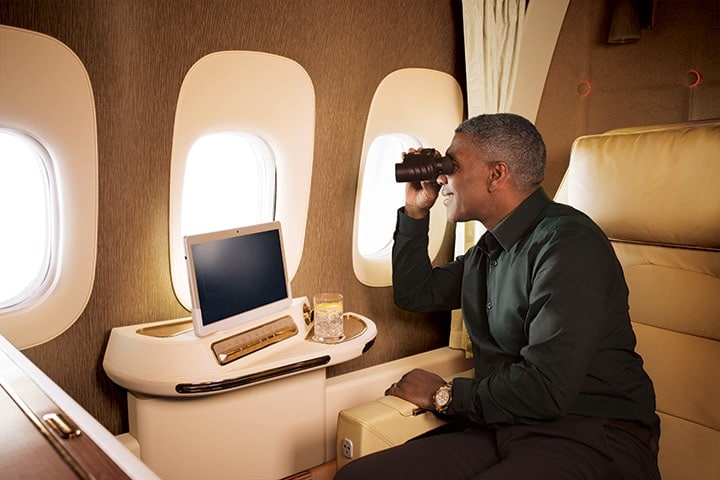 A man sitting in Emirates First Class on Boeing 777 uses the binoculars to view through his window