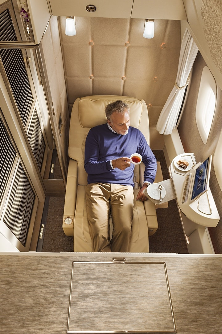 Man having a cup of tea in Emirates First Class looking out of the window