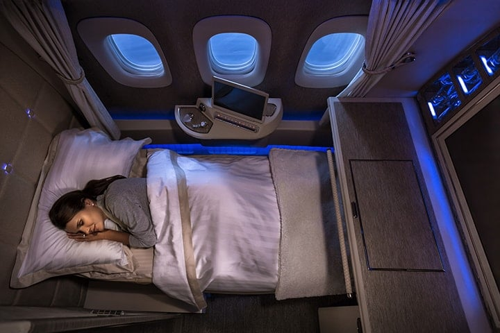 A woman sleeps on her fully flat bed in the Emirates First Class on the Game Changer Boeing 777