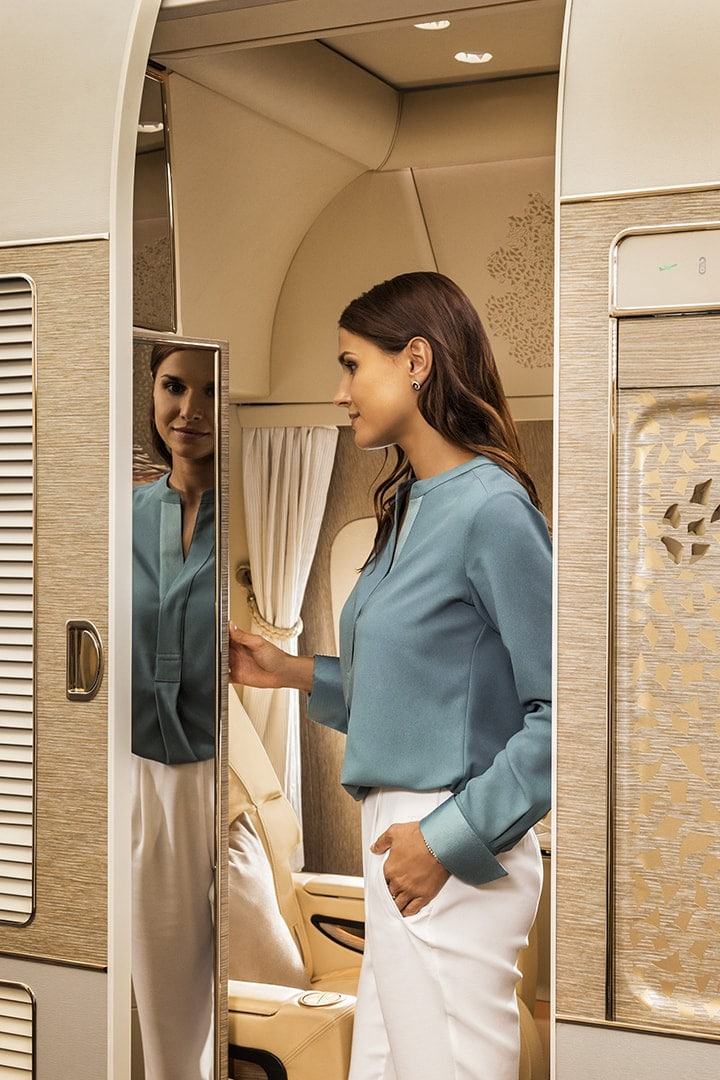 Woman views her reflection on the full-length mirror in Emirates First Class cabin on the Game Changer Boeing 777