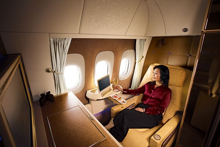 A woman using her touchscreen pad in Emirates First Class on the Game Changer Boeing 777