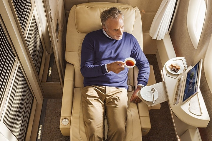 A man reclined in his seat enjoying a warm beverage with biscuits on the side