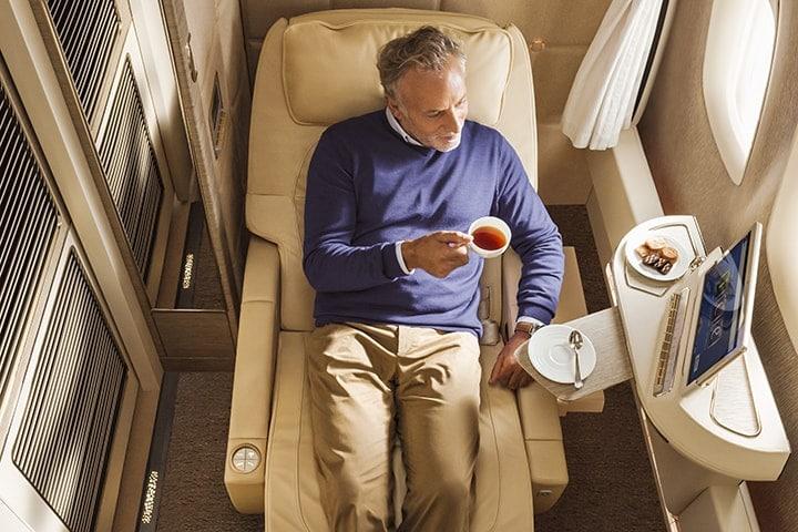 Bir adam, koltuğunda yanında bisküvilerle sıcak içeceğinin tadını çıkarıyor